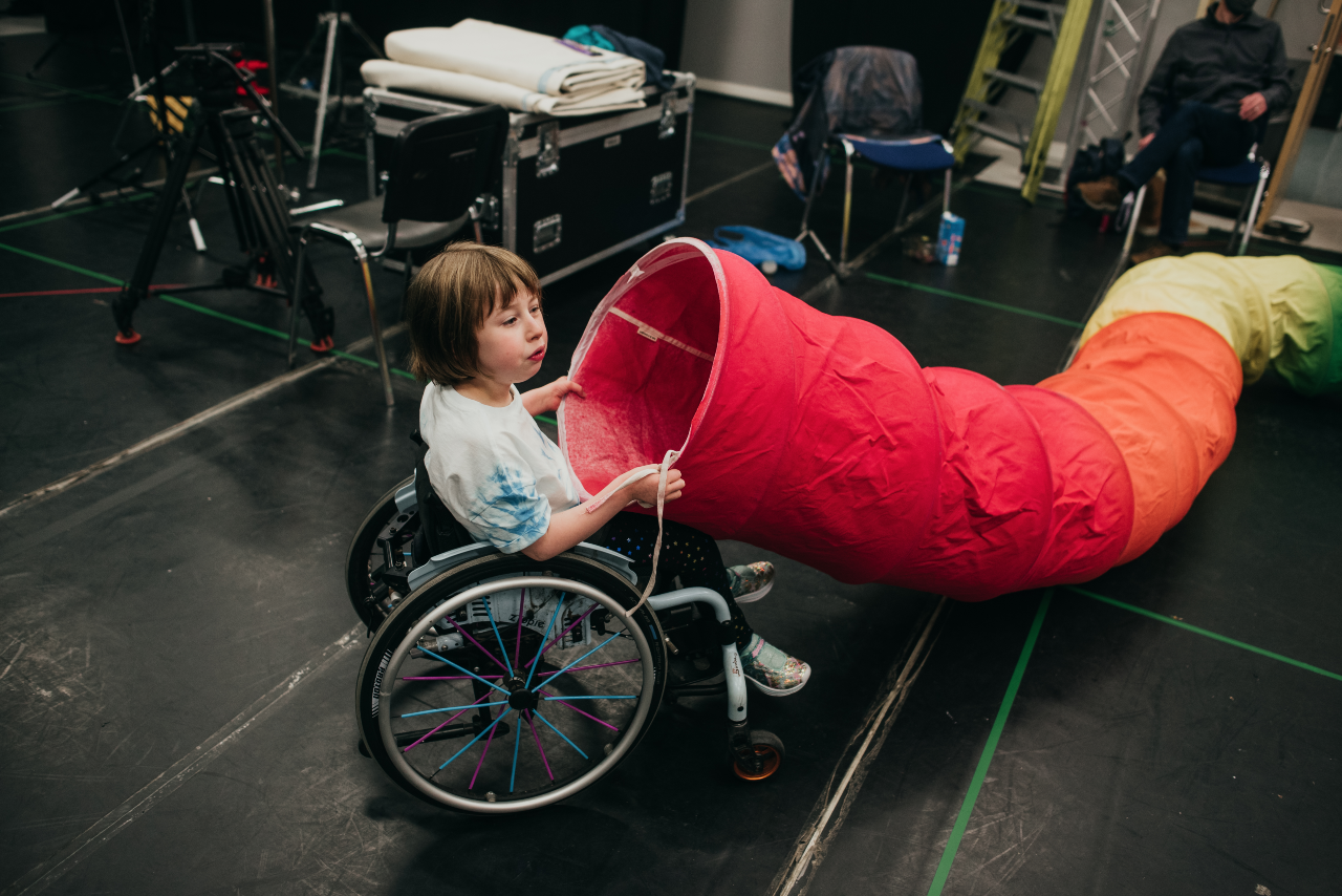 Oona sits backstage. She is holding a large red and green tube in their hands as if about to dunk her head in the end. It is about large enough for a person to crawl through.