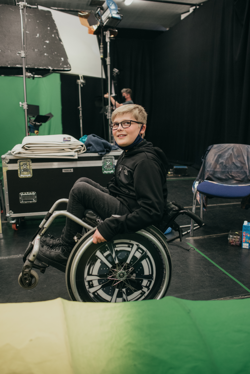 A photo of Ollie backstage. He is doing a wheelie on the large back wheels of his wheelchair with the small front two up in the air. He has a facemask pulled down at his chin
