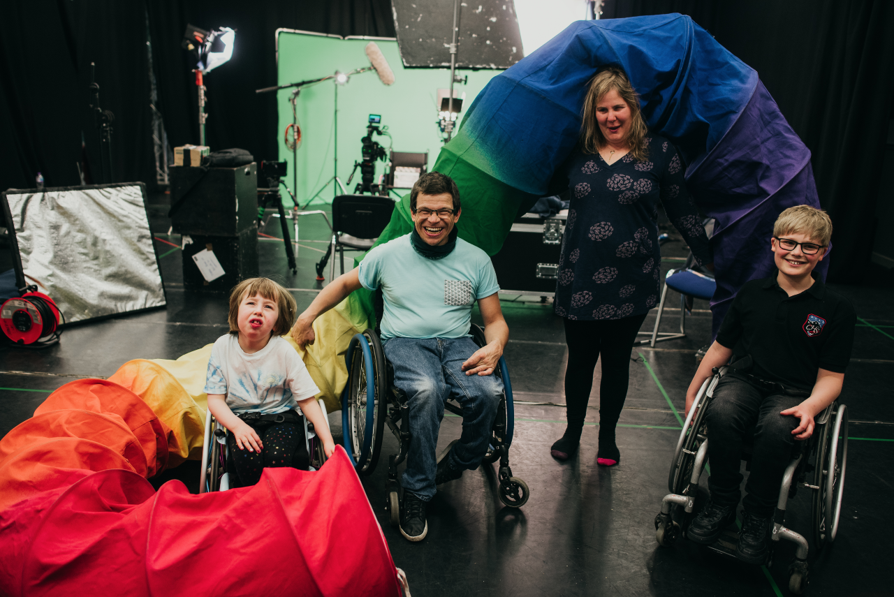 Sal, Rob, Oone and Ollie pose with big smiles, and smile for a photograph. They are backstage and there is lighting and sound equipment in the background all set against a greenscreen. They are posing with a large rainbow tube around them.