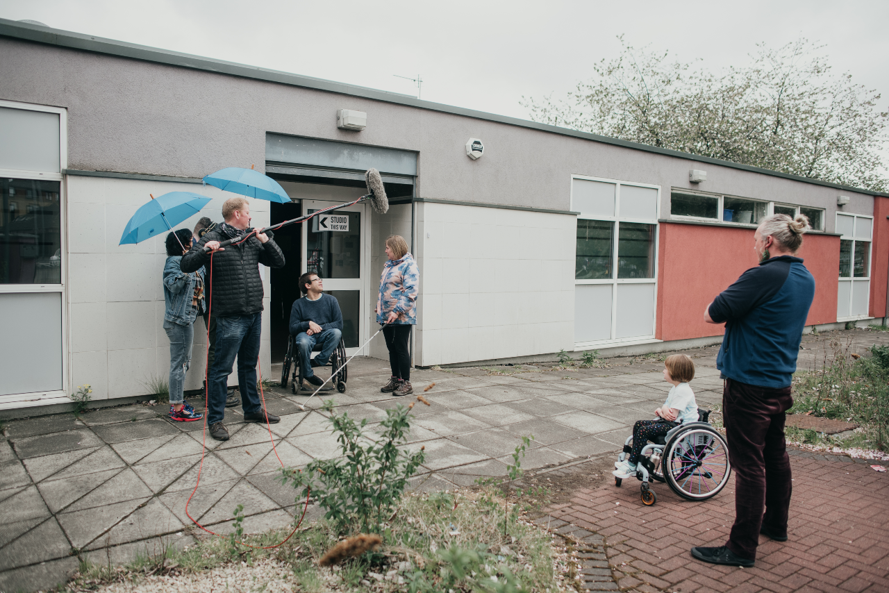 A photo taken outside of a small building. Rob and Sal are surrounded by a camera crew. There is a camera and a mic on a boom pointed at them. Joe and Oona watch on from a distance.