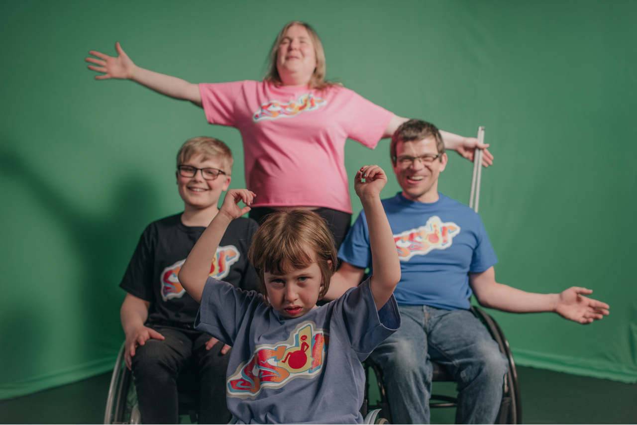 Sal, Rob, Ollie and Oona pose in front of a green screen in a diamond formation. They are all wearing different coloured T shirts that have 'SSDR' written on them. Sal is at the back, smiling with her arms outstretched and a folded cane in one hand. In front of her there are Roba dn Ollie, who are both smiling. At the very front is is Oona, who has her arms in the air.